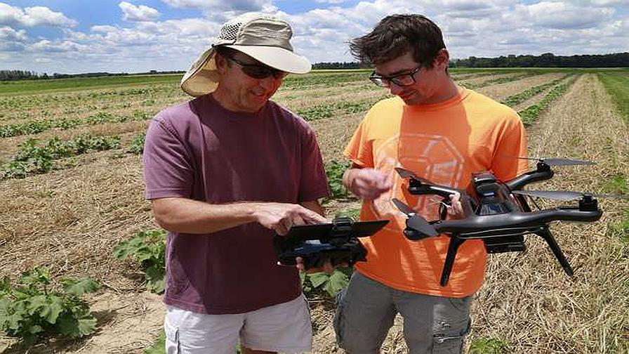 Logan Dyer, right, a Precision Ag student at Clark State, talks with Ohio State University associate professor James Jasinski about the drone they've been using to map their pumpkin field at the OSU Research Farm Tuesday. (Photo Credit: Dayton Daily News Staff/Bill Lackey